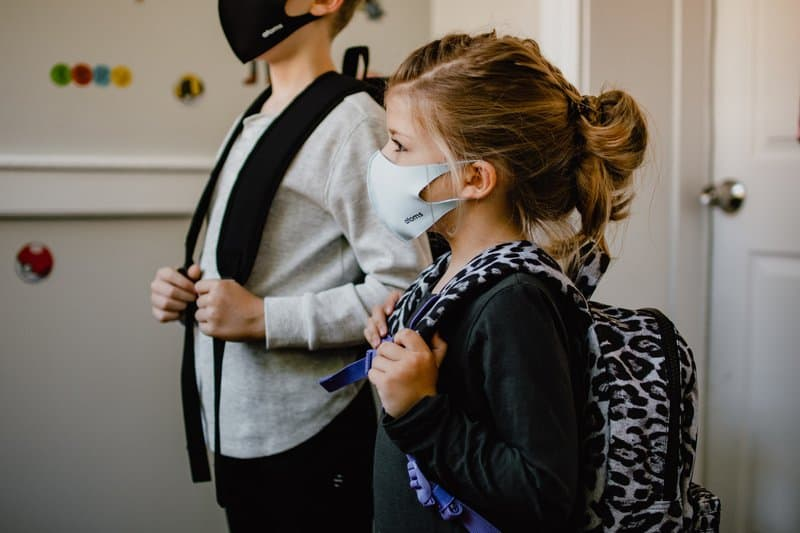 two kids standing side by side wearing masks